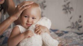 Młoda piękna kobieta ściska jej ślicznej córki z zabawką w berroom - macierzyństwa pojęcie zdjęcie wideo