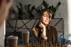 młoda piękna kobieta bawić się szachy podczas gdy słońca jaśnienie fotografia stock