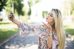 Młoda piękna kobieta bierze selfie na telefonu komórkowego obsiadaniu na trawie w lata miasta parku Ciosu buziak plenerowy Obrazy Royalty Free
