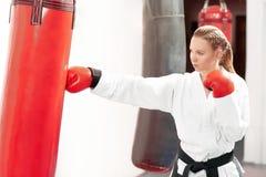 Młoda piękna kobieta boksuje ciężką czerwoną torbę z silnym kopie wewnątrz gym obraz stock