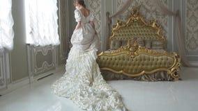 Młoda piękna kobieta chodzi ogromny złoty łóżko w białego rocznika balowym kostiumu z długą pociąg suknią zbiory