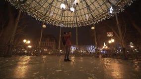 Młoda piękna kobieta chodzi przy nocą w mieście, fotografuje Bożenarodzeniowe dekoracje Przygotowanie dla świętować nowego roku zbiory