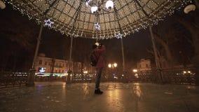Młoda piękna kobieta chodzi przy nocą w mieście, fotografuje Bożenarodzeniowe dekoracje Przygotowanie dla świętować nowego roku zbiory wideo