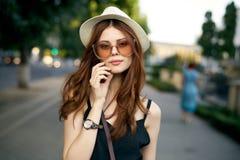 Młoda piękna kobieta chodzi wzdłuż głównej ulicy w mieście w białych kapeluszowych i są ubranym okularach przeciwsłonecznych zdjęcie stock