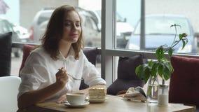 Młoda piękna kobieta cieszy się fragrant kawy i cukierki tortowego obsiadanie w kawa domu Biznesowa kobieta odpoczywa podczas prz Obrazy Royalty Free