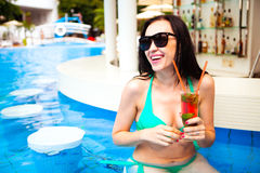 Młoda piękna kobieta cieszy się koktajl w basenu barze przy tropikalnym zdjęcie royalty free