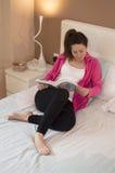 Młoda piękna kobieta czyta książkę w sypialni Zdjęcie Stock