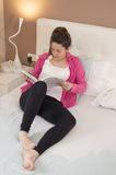 Młoda piękna kobieta czyta książkę w sypialni Fotografia Royalty Free