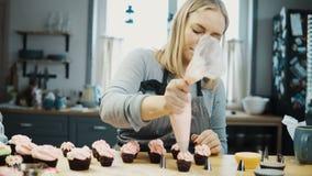 Młoda piękna kobieta dekoruje małe babeczki z śmietanką od ciasta zdojest Blondynki cukierniczka przygotowywa rozkaz zbiory wideo