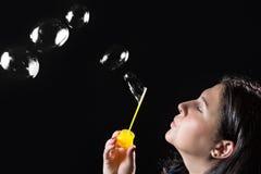 Młoda piękna kobieta dmucha mydlanych bąble na czarnym tle zdjęcia royalty free