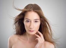Młoda piękna kobieta dotyka jej twarz Fotografia Stock
