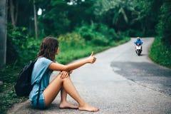 Młoda piękna kobieta hitchhiking siedzieć na drodze Obraz Stock