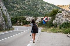 Młoda piękna kobieta hitchhiking stać na drodze z czarnym plecakiem Piękny młody żeński autostopowicz drogą podczas vacat obraz stock