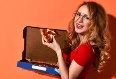 Młoda piękna kobieta je pepperoni pizzy plasterek i trzyma całą pizzę w pudełku na pomarańcze Fotografia Stock