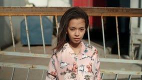 Młoda piękna kobieta jest ubranym bombowiec kurtkę pozuje nad metalu ogrodzeniem zbiory wideo