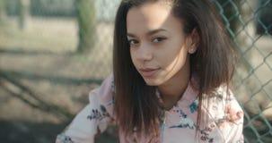 Młoda piękna kobieta jest ubranym bombowiec kurtkę pozuje nad metalu ogrodzeniem zbiory