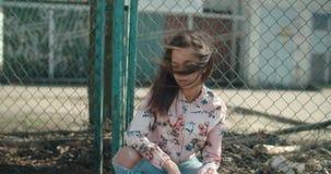 Młoda piękna kobieta jest ubranym bombowiec kurtkę pozuje nad metalu ogrodzeniem zdjęcie wideo