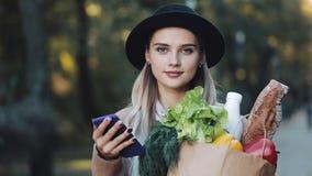 Młoda piękna kobieta jest ubranym elegancką żakiet pozycję w jesień parka mienia pakunku produkty i używa smartphone zbiory wideo