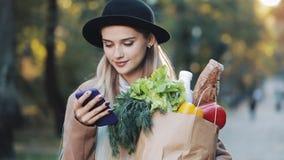 Młoda piękna kobieta jest ubranym elegancką żakiet pozycję w jesień parka mienia pakunku produkty i używa smartphone zbiory
