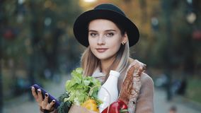 Młoda piękna kobieta jest ubranym elegancką żakiet pozycję w jesień parka mienia pakunku produkty i używa smartphone zdjęcie wideo