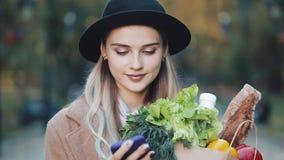 Młoda piękna kobieta jest ubranym elegancką żakiet pozycję w parkowym mienie pakunku produkty i używa smartphone głos zbiory