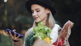 Młoda piękna kobieta jest ubranym elegancką żakiet pozycję w parkowym mienie pakunku produkty i używa smartphone głos zbiory wideo