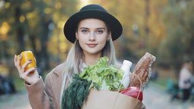 Młoda piękna kobieta jest ubranym elegancką żakiet pozycję w parkowym mieniu pakunek produkty uśmiechnięci i patrzeje w zbiory wideo