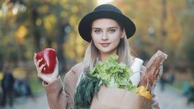 Młoda piękna kobieta jest ubranym elegancką żakiet pozycję w parkowym mieniu pakunek produkty uśmiechnięci i patrzeje w zdjęcie wideo