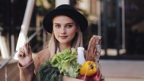 Młoda piękna kobieta jest ubranym elegancką żakiet pozycję w ulicie z pakunkiem produktów i chwytów karta kredytowa zbiory wideo