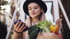 Młoda piękna kobieta jest ubranym elegancką żakiet pozycję w ulicznym mienie pakunku produkty i używa smartphone głos zbiory wideo