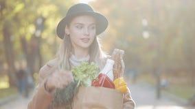 Młoda piękna kobieta jest ubranym eleganckiego żakieta odprowadzenie w parkowym mieniu pakunek produkty uśmiechnięci i patrzeje w zdjęcie wideo
