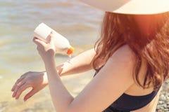 Młoda piękna kobieta mażąca z sunscreen na plaży Śmietanka na skórze w postaci krzyża Pojęcie ochrona od fotografia royalty free