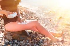 Młoda piękna kobieta mażąca z sunscreen na plaży Czerwona skóra na nogach Cieki zamykaj? up Pojęcie ochrona od słońca zdjęcia stock
