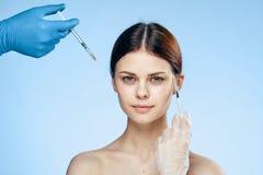 Młoda piękna kobieta na błękitnym tle trzyma strzykawkę, medycyna dojrzały ponad operacji plastycznej białą kobietą Obraz Royalty Free