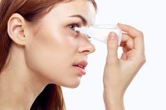 Młoda piękna kobieta na białym odosobnionym tła obcieknięciu w oka oka kroplach fotografia royalty free