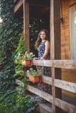 Młoda piękna kobieta na drewnianym balkonie, trzyma ręki na poręczu Wokoło jej kwiatów i natury obraz royalty free