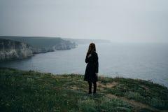 Młoda piękna kobieta na falezie góra blisko morza, smucenie Obrazy Royalty Free