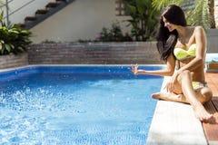 Młoda piękna kobieta na stronie basen bawić się z wodą Obrazy Stock