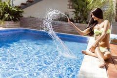 Młoda piękna kobieta na stronie basen bawić się z wodą Zdjęcia Royalty Free