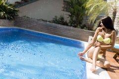 Młoda piękna kobieta na stronie basen bawić się z wodą Fotografia Royalty Free