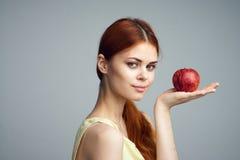 Młoda piękna kobieta na szarym tle trzyma jabłka, owoc, dieta Obrazy Royalty Free