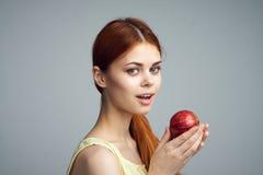 Młoda piękna kobieta na szarym tle trzyma jabłka, owoc, dieta Obraz Royalty Free