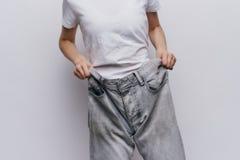 Młoda piękna kobieta na tła lekkich chwytach dyszy, sporty, dieta, ciężar strata, postęp Obrazy Royalty Free