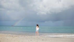 Młoda piękna kobieta na tropikalnym seashore z tęczą na tle Szczęśliwa dziewczyna relaksuje przy białego piaska tropikalną plażą zdjęcie wideo