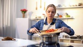 Młoda piękna kobieta nieszczęśliwa z kucharstwem w kuchni zanudzającej i męczącej obowiązek domowy, obrazy stock