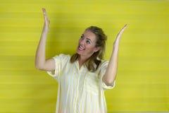Młoda piękna kobieta ono uśmiecha się nad odosobnionym tłem pokazywać oba ręki otwiera palmy obraz royalty free