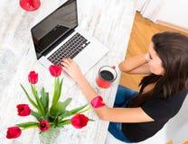 Młoda piękna kobieta ono uśmiecha się podczas gdy używać laptop w domu obrazy royalty free