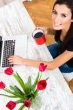 Młoda piękna kobieta ono uśmiecha się podczas gdy używać laptop w domu Zdjęcie Royalty Free