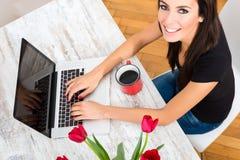 Młoda piękna kobieta ono uśmiecha się podczas gdy używać laptop w domu Zdjęcie Stock