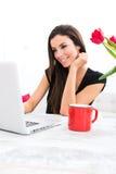 Młoda piękna kobieta ono uśmiecha się podczas gdy używać laptop w domu Fotografia Royalty Free